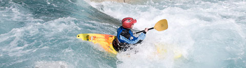 River grading. A kayaker paddles down a large wave on a grade three artificial white water course
