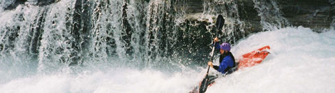 A kayaker paddles over a very large wave into a maelstrom of white water, as water pours from the gorge walls beside him. Grade five water in the French Alps.