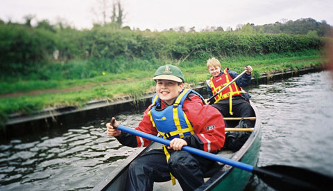 Canoe lessons for children in London. Two smiling boys paddle an open canoe on a canal.