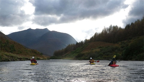Three kayakers paddle a wide, remote river in Scotland