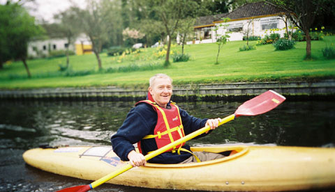 Canoe touring and recreation. A middle aged man enjoys paddling a kayak on a calm river/