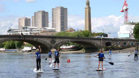 Stand Up Paddle Boarders enjoying London Paddleboarding at Brentford Boating Arch on the River Thames.